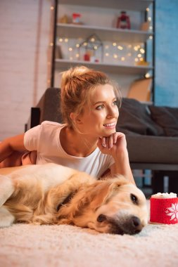 beautiful young blonde woman lying on fluffy rug with golden retriever dog and propping chin with hand at christmas time