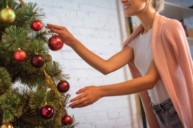 cropped view of young woman decorating christmas tree with baubles