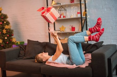 happy young blonde woman lying on couch and throwing up present in air at christmas time