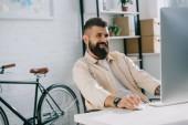 Usmívající se podnikatel sedí v moderní kanceláři a při pohledu na monitor
