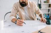 Szakállas építész ülő-on iskolapad és a munka tervrajzok