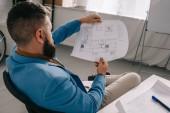 Mužské architekt sedí a při pohledu na plán v moderní kanceláři