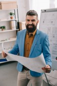 Pohledný architekt, usmíval se a držení modrotisk v moderní kanceláři