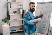 Photo handsome adult male architect in blue formal wear holding blueprint, using flip chart and working on project in office