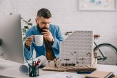 Photo focused adult male architect in formal wear holding cup of coffee and working on project in office