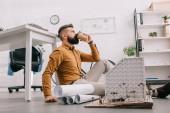 vousatý dospělých mužských architekt popíjel kávu jít a pracují na projektu stavby s plány v úřadu