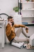 Fotografie usmívající se vousatý dospělých mužských architekt mluví o smartphone, držel kávu jít a pracovat na plány, které v úřadu