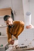 zaměřil vousatý dospělých mužských architekt hospodářství blueprint, ukazuje na house modelu a pracují na projektu v úřadu