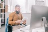Fotografie zaměřil dospělých obchodní muž sedí v kanceláři a používání digitálních tabletu na pracovišti