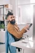 s úsměvem dospělých obchodní muž sedí v kanceláři a používání digitálních tabletu na pracovišti