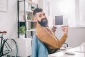 pohledný dospělých obchodní muž sedí v kanceláři a používání digitálních tabletu na pracovišti