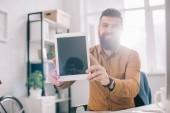 s úsměvem dospělých obchodní muž představující digitální tabletu s prázdnou obrazovkou na pracovišti s podsvícením