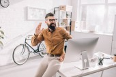 Fotografie cheerful bearded adult businessman sitting at office desk, looking away and waving