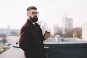 Fotografie zaměřil stylové muže v brýlích drží kávu jít na střeše