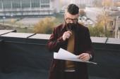Fotografie zamyšlený dospělých mužských architekt v brýlích drží blueprint a pracuje na projektu na střeše