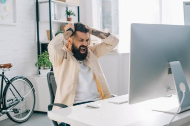 Impulsive bearded businessman with hands on head sitting at computer desk and screaming in office
