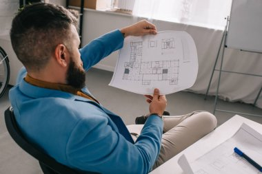 Male architect sitting and looking at blueprint in modern office stock vector