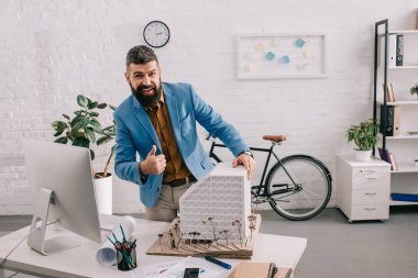 busy adult male architect in formal wear working on project at computer desk in office