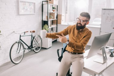 happy bearded adult businessman holding cup of coffee and pointing finger in exitement at workplace