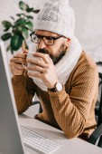 Fotografie sick businessman in scarf and knitted hat working at computer desk and drinking tea in office