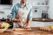 vágott lövés a mosolygó fiatal férfi-kötény tartja a kést, és a kezét a vágódeszka a konyha