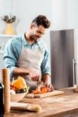 mosolygó fiatal férfi-kötény vágódeszka a konyha friss zöldségekkel