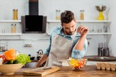 csinos, fiatal férfi-kötény növényi saláta só hozzáadásával konyhában főzés közben