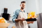 nízký úhel pohled usmívající se mladý muž v zástěře drží pánev se zeleninou