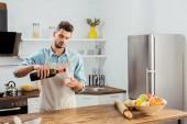Fotografia giovane bello in grembiule, versare il vino in cucina