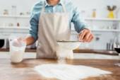 Teilansicht von jungem Mann in Schürze, der Mehl auf Küchentisch sichtet