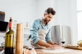 Fotografie low angle view of focused young man in apron preparing dough in kitchen