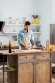 pohledný mladý muž v zástěře Příprava těsta v kuchyni