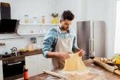 Fényképek csinos, fiatal férfi-kötény konyhában tészta elkészítése