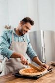 usmíval se mladý muž v zástěře řezání čerstvé domácí pizza na plech