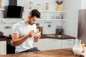 Fotografie mladý muž v pyžamu jí Kukuřičné vločky k snídani doma