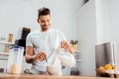 Fotografie usmíval se mladý muž vylévající mléka do misky s corn flakes