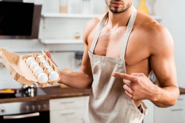 Cropped shot of sexy bare-chested man in apron pointing with finger at egg carton stock vector