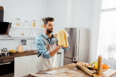 handsome young man in apron holding uncooked dough while preparing pizza