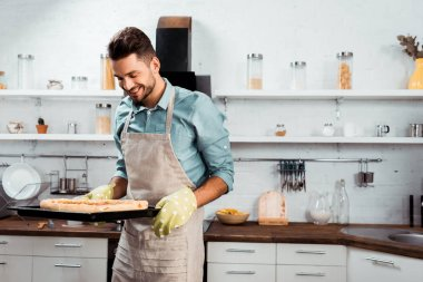 smiling young man in apron and potholders holding baking tray with fresh homemade pizza