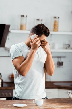 frustrated young man rubbing nose bridge and talking by smartphone at morning in kitchen