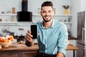 schöner junger Mann hält Smartphone mit leerem Bildschirm in der Küche und lächelt in die Kamera