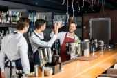 Fotografie handsome barmen in aprons high five at workplace