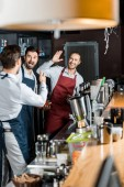 Fotografie cheerful barmen in aprons high five at workplace