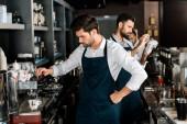 erwachsene hübsche Barista in Schürze Kaffee kochen am Arbeitsplatz