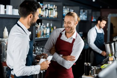 cheerful smiling barmen standing with arms crossed at workplace while coworker polishing glass
