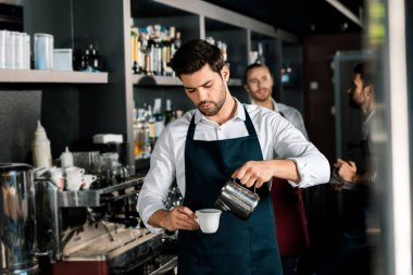 adult barista in apron pouring milk to coffee at workplace