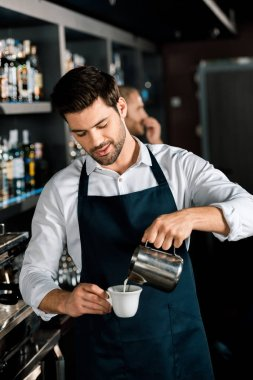 handsome barista in apron pouring milk from jar at workplace