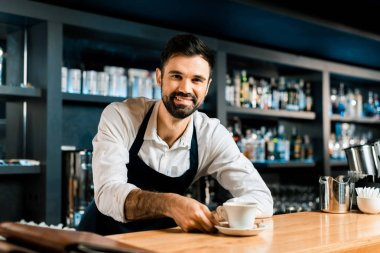 cheerful smiling barista with coffee at wooden counter