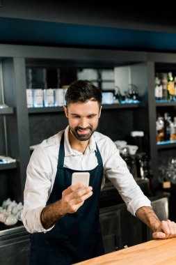 Barman standing with smartphone and smiling in bar stock vector