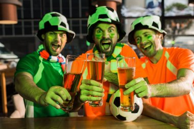 Football fans holding glasses with beer and screaming in bar